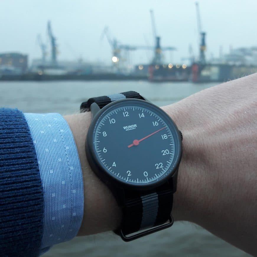 Wristshot der Wundrwatch. Im Hintergrund sieht man die Kräne und Docks von Blohm+Voss in Hamburg.